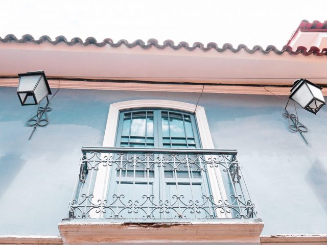 Colonial balconies and lanterns line the alley in various hues